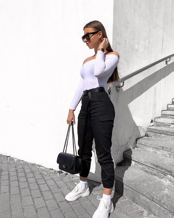 a monochromatic outfit with black cargo pants, a white off the shoulder top, white trainrs and a black bag