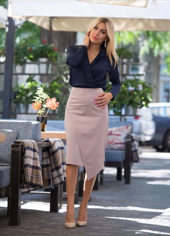 a navy wrap blouse with long sleeves, a blush asymmetrical pleated skirt, nude shoes for work
