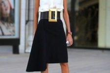 a refined monochromatic look with a sleeveless shirt, a black asymmetrical skirt, two tone shoes and a statement belt