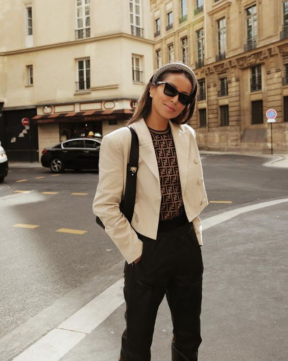 a refined outfit with black pants, a printed top, a white cropped blazer, a black bag