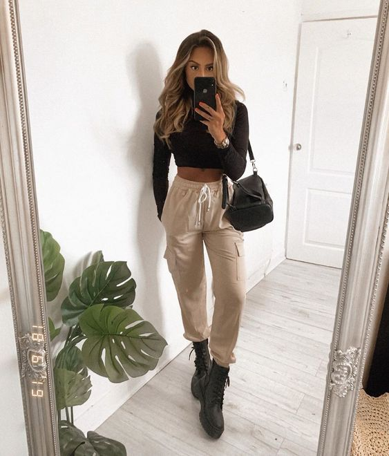 a sexy look with a black crop top with long sleeves, tan cargo pants, black army boots and a black bag
