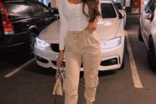 a sexy look with a white fitting button up top, tan cargo pants, lace up shoes and a matching bag