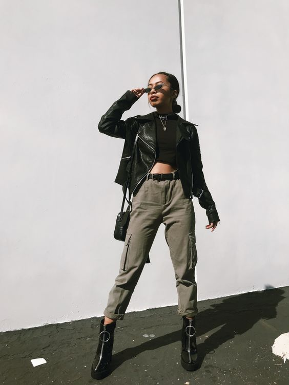 a sexy spring outfit with a black crop top, olive green cargo pants, a black leather jacket and black booties