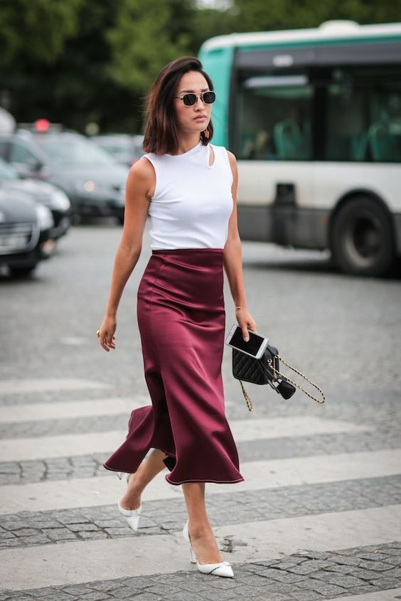 a spring to summer look with a cutout sleeveless top, a burgundy slip midi skirt, white shoes and a black bag