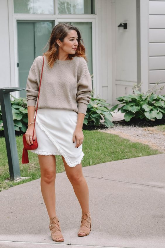 a spring to summer work look with a neutral top, a white fringe asymmetrical skirt, tan lace up shoes and a red bag