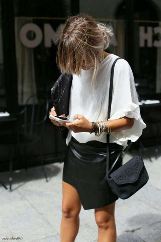 a statement monochromatic work look with an oversized white tee, a black leather asymmetrical mini, a black bag