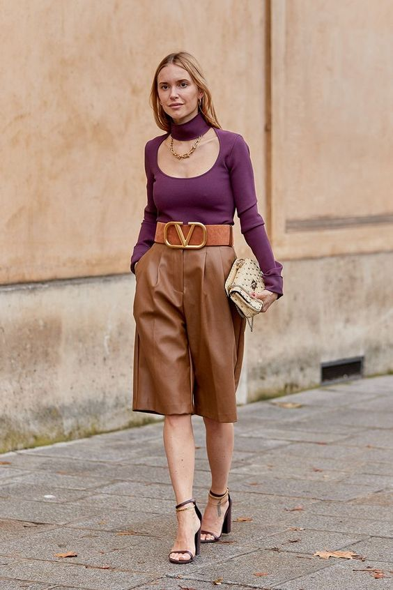 a statement outfit with a purple cutout top, a statement necklace, brown bermudas, brown shoes and a clutch