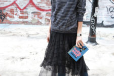 a striped long sleeve top, blue jeans, a black sheer lace skirt, pink shoes and a quirky clutch