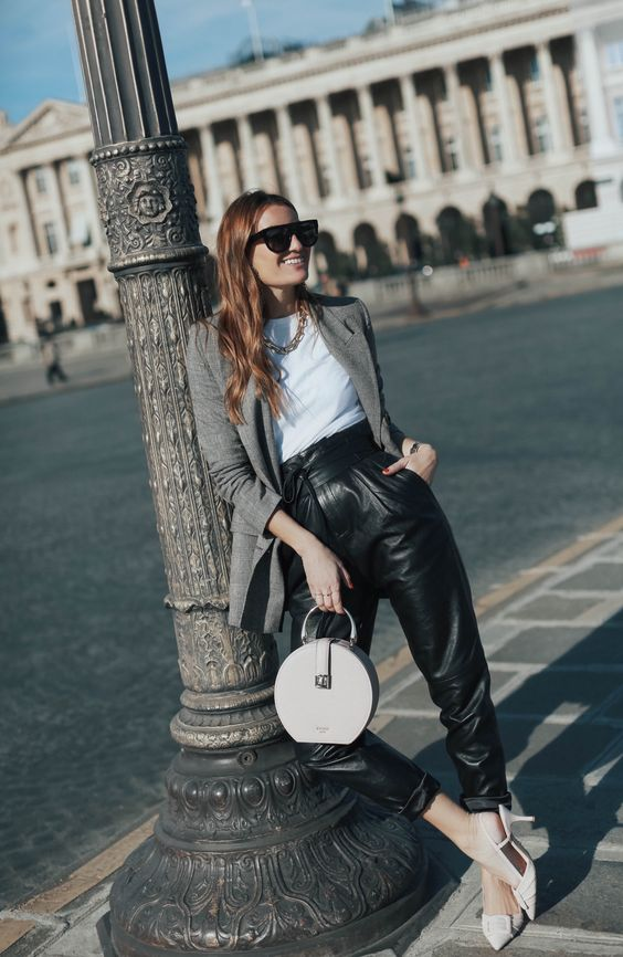 a stylish work look with a white tee, blakc high waisted leather pants, white shoes, a long grey blazer and a white round bag