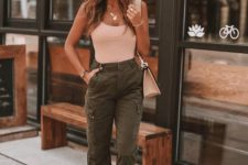 a summer look with a blush top, green cargo pants, white shoes and a blush bag to try