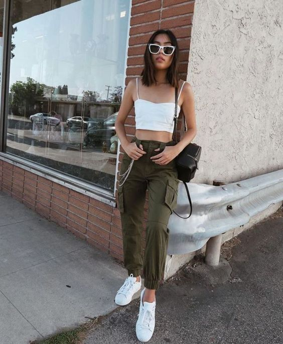 a summer look with green cargo pants, white sneakers and a crop top and a black backpack