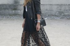 a total black look with a bodycon mini dress, a sheer pompom skirt, black boots, a leather jacket and a hat