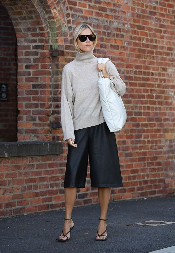 a trendy look with a neutral turtleneck, black leather bermudas, black strappy heels, a large statement bag