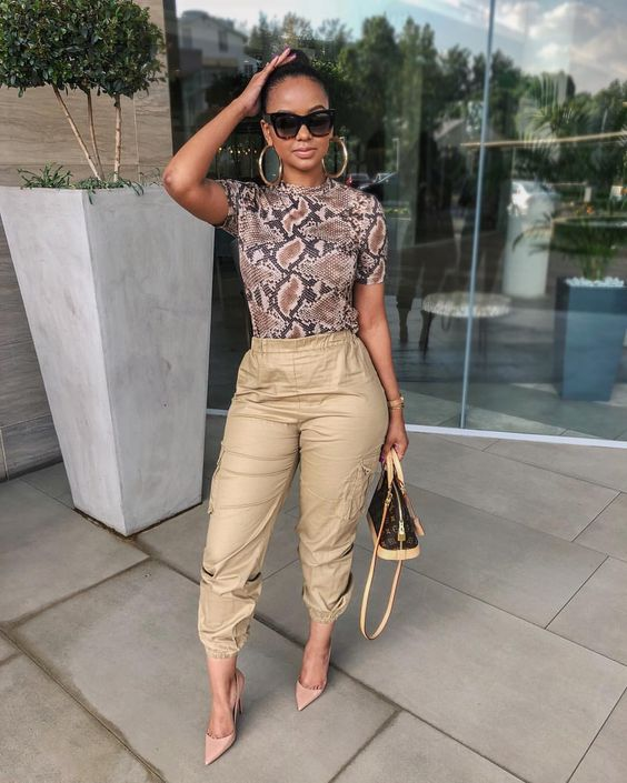 a trendy outfit with a snakeskin top, tan cargo pants, blush shoes and a comfy bag