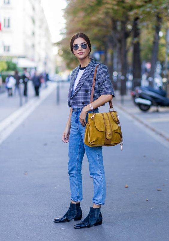 a trendy spring look with a white tee, a cropped blazer, blue jeans, navy booties and a mustard bag