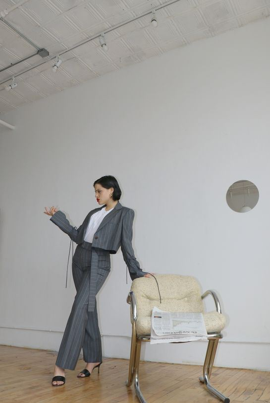 a trendy work look with a white tee, a grey striped pantsuit with a cropped blazer and black heels
