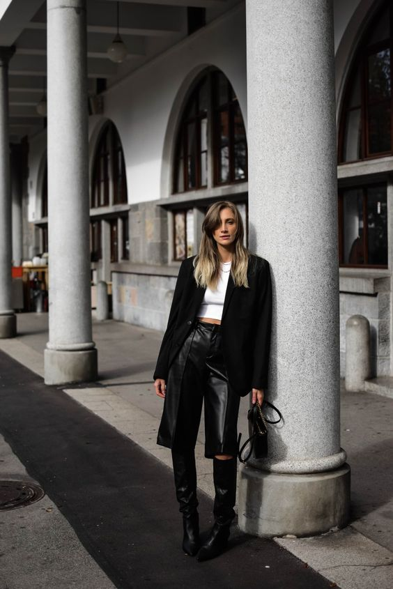 a white crop top, a black blazer, black leather bermudas, black boots and a small bag for a trendy look