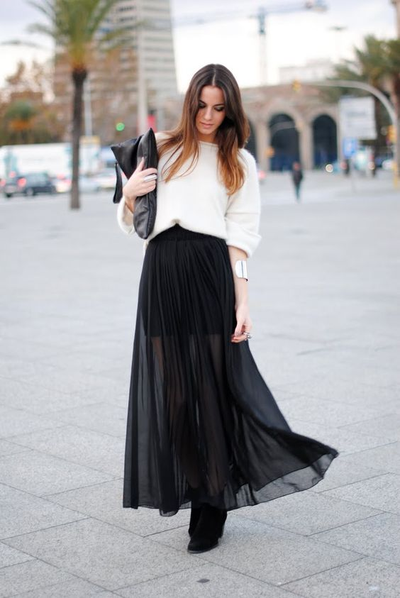 a white oversized top, a black mini skirt, a black sheer pleated overskirt, black booties and a clutch