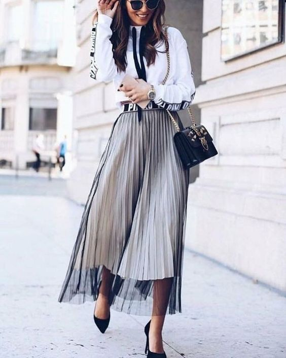a white printed shirt, a white pleated midi skirt, a sheer black overskirt, black shoes and a bag