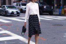 a white shirt, a windowpane print asymmetrical midi skirt, blue shoes and a black bag