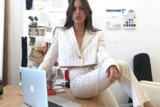 a white striped pantsuit with a cropped blazer and heels for a bold statement work look