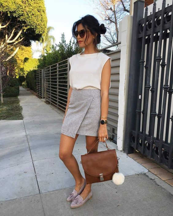 a white top, a grey asymmetrical mini skirt, lavender flats and a brown bag for a summer work look