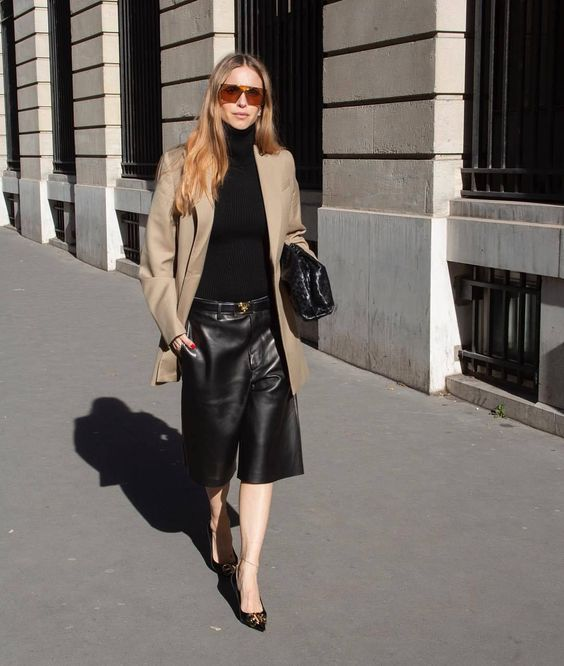 a work look with a black turtleneck, black leather bermudas, a tan oversized blazer, sheer black shoes and a black bag