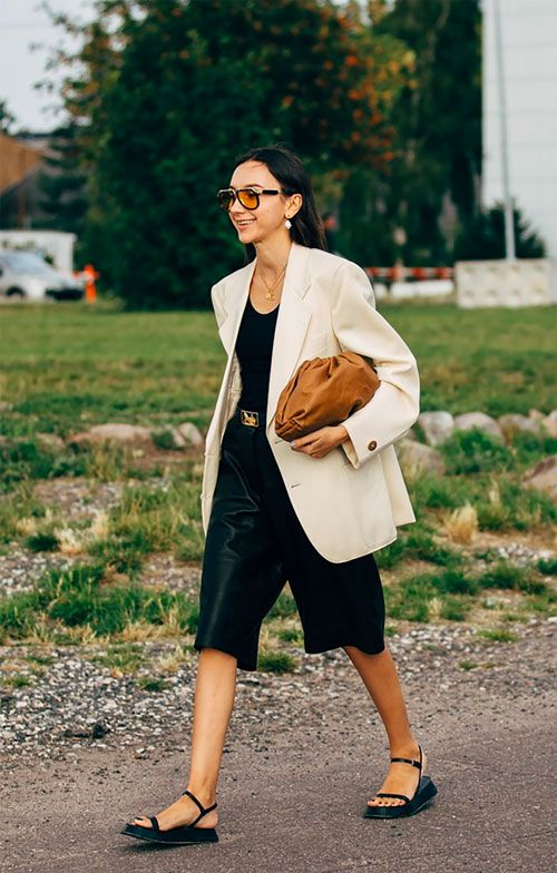 a work outfit with a black top, black leather bermudas, an oversized creamy blazer, black sandals and a brown clutch