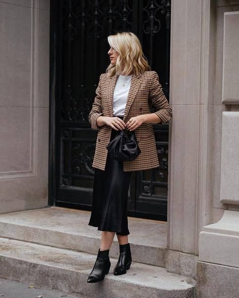 a work outfit with a white tee, a plaid oversized blazer, a black slip midi, black booties