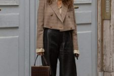 an edgy work outfit with a tan shirt, a plaid cropped blazer, leather bermuda shorts, black booties and a bag