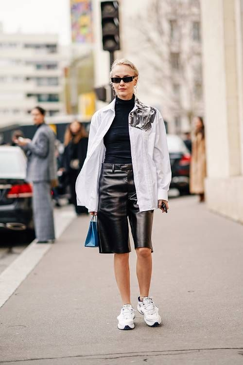 an everyday look with a black turtleneck, a white oversized jacket, white trainers, black leather bermudas and a blue bag