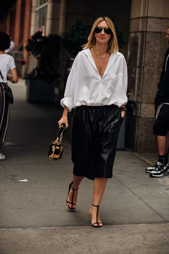 an oversized white shirt, oversized black bermuda shorts, black strappy heels and a printed bag