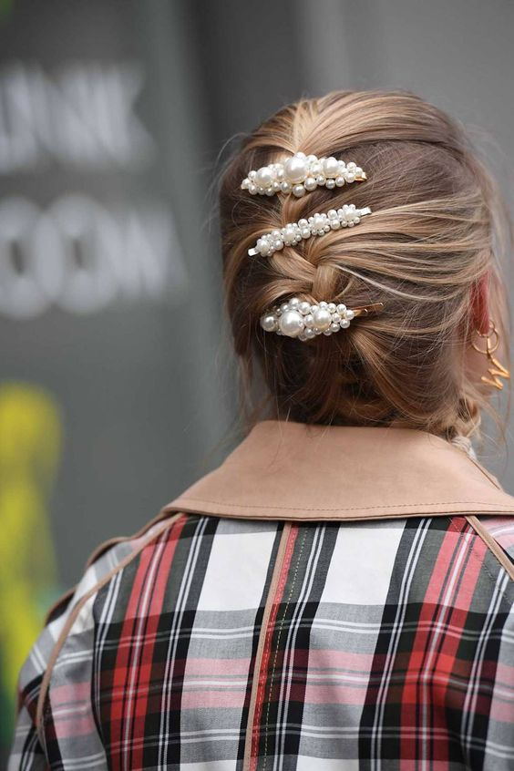 medium hair styled into a messy braided updo and accented with three matching pearl barrettes is a stylish idea