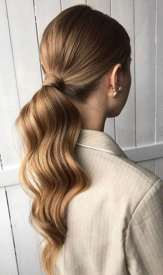 a wavy low ponytail with a sleek top is a cool and stylish idea for a modern girl