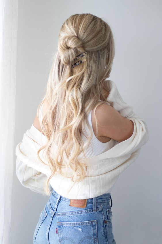 a half updo with a twisted bun and waves down plus a large hairpiece for a trendy look