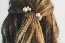 06 a messy and textural half updo with a braid and a bump plus statement pearl hairpins