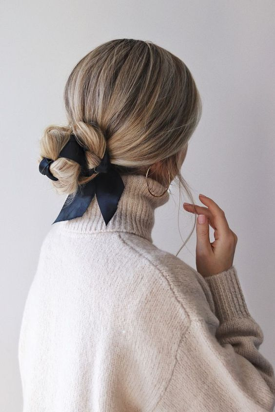 a low twisted updo all tied up with a navy ribbon and with a sleek top is a chic and girlish idea