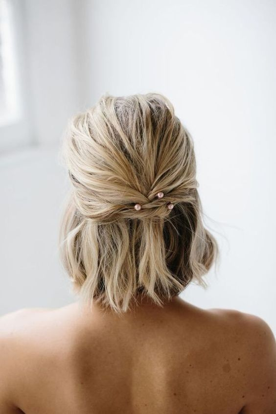 a short half updo with twists secured with pink pearl hair pins and a messy top