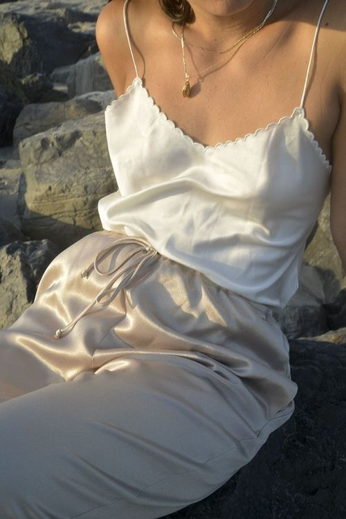 a white spaghetti strap top with a scallop edge and matching silk pants to rock