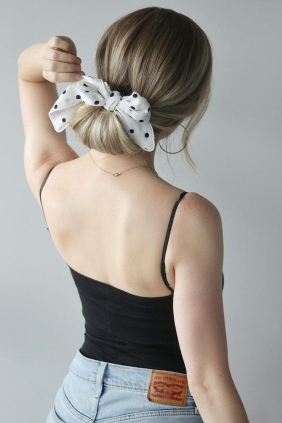a simple twisted low chignon with a polka dot hair bow is a cool idea with a retro feel