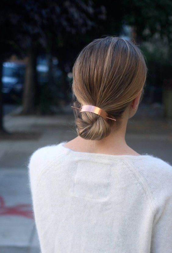 a sleek low bun with a sleek top secured with a copper hair cuff is a stylish and minimal idea