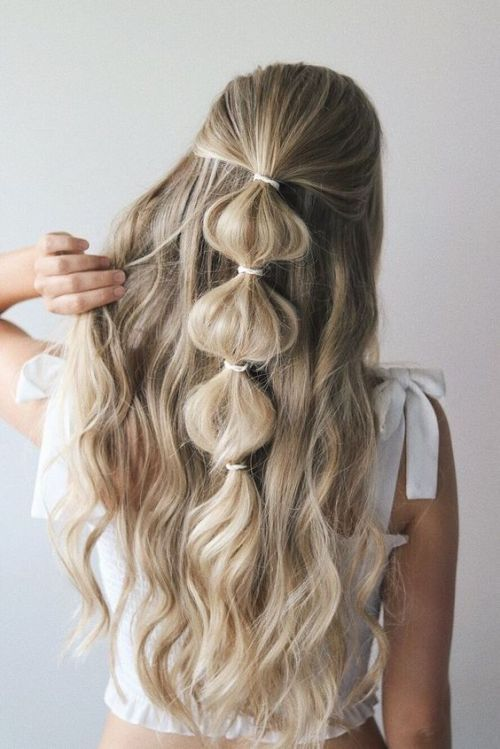 an easy half updo with a bubble braid and waves is a romantic and boho option to go for