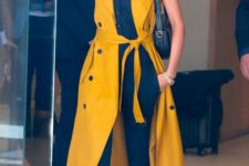 Victoria Beckham rocking a black top, black skinnies, a sunny yellow sleeveless midi shirt dress looks wow