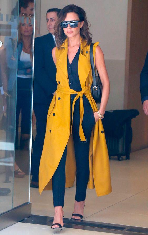 Victoria Beckham rocking a black top, black skinnies, a sunny yellow sleeveless midi shirt dress looks wow