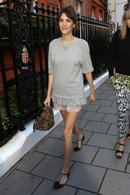 With beige shorts, gray ruffled sweatshirt and leopard bag