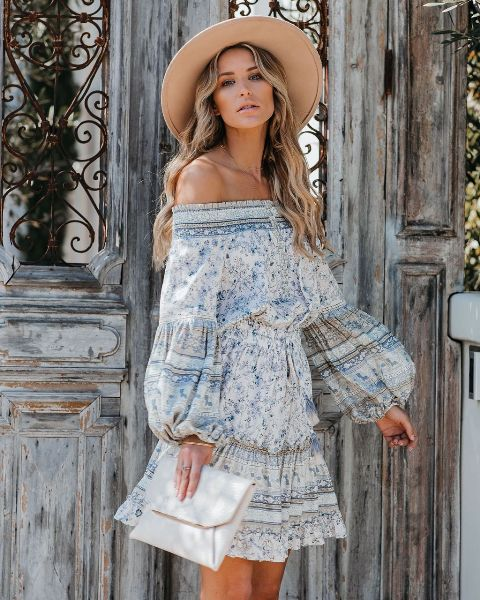 With beige wide brim hat and white clutch