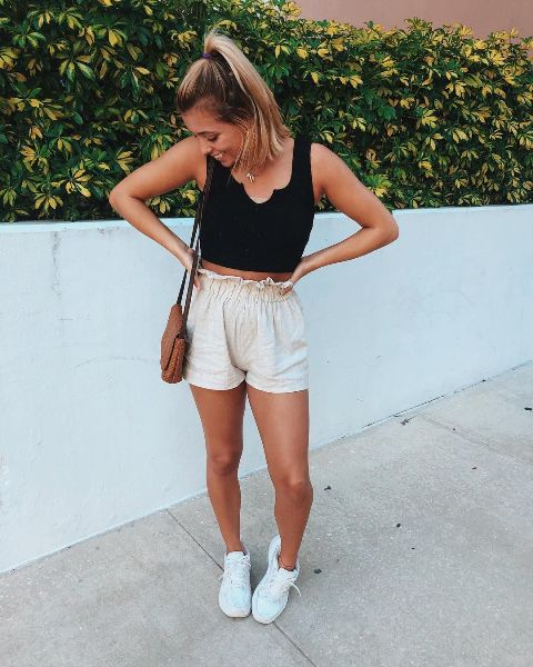 With black crop top, brown bag and white sneakers