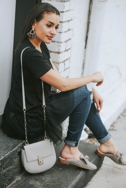 With black lace shirt, cuffed jeans and light gray bag