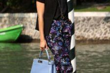 With black shirt, black jacket, light blue bag and floral pants