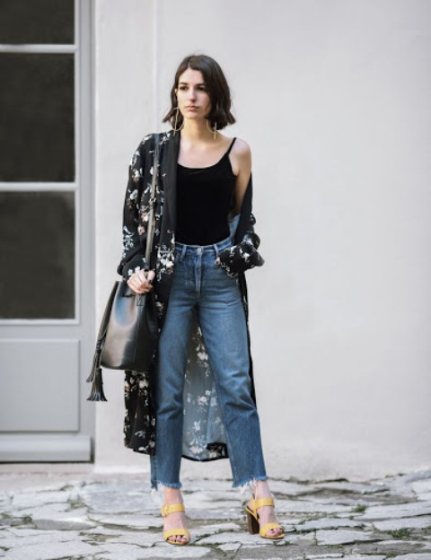 With black top, black leather bag, distressed jeans and yellow sandals